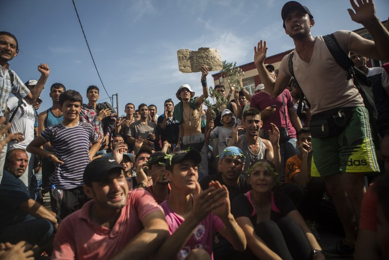 Refugees and migrants take part in a protest to demand faster processing by local authorities of their registration and the issuing of travel documents at the port of Mytilene on the northeastern Greek island of Lesbos.