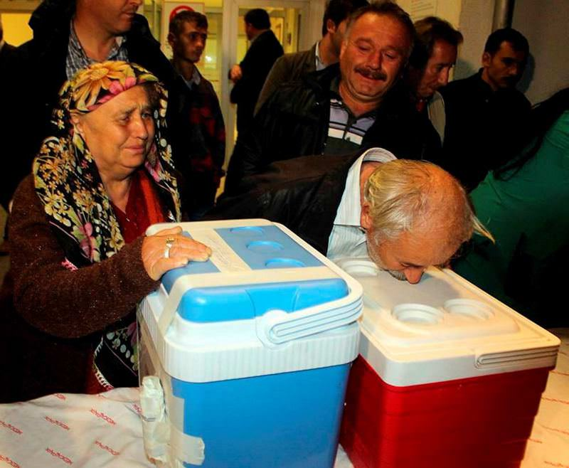 Relatives of a deceased man who donated his organs in the city of Ordu embracing the coolers carrying his organs.