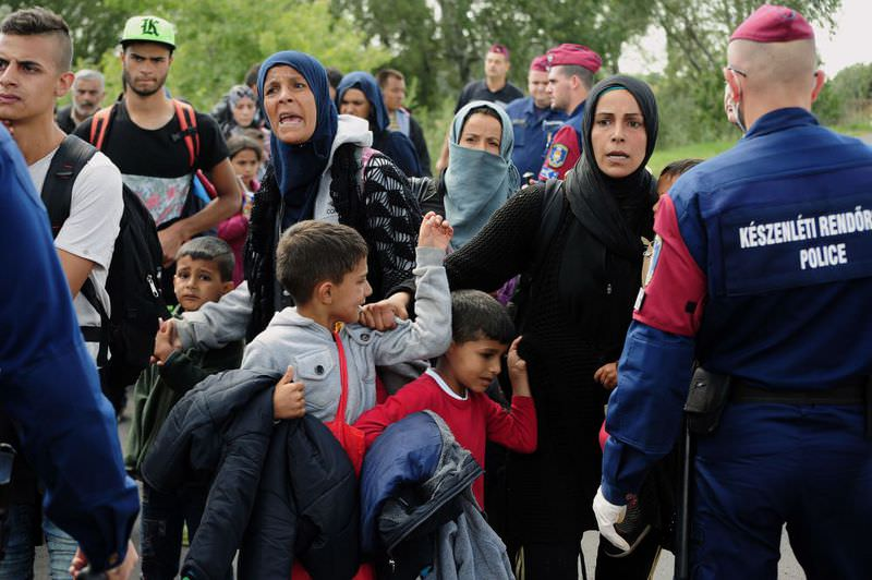 Police officers stop a group of migrants after a migrant crowd broke out of a collection point near Roszke on the Hungarian-Serbian border.