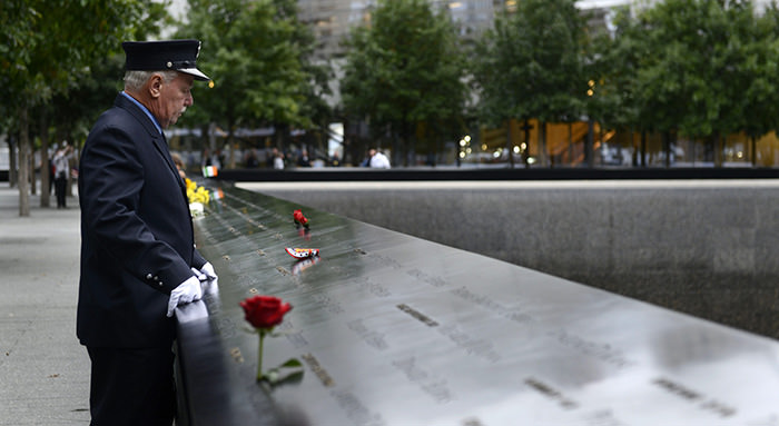 A firefighter pauses at a loved one's name along the South Pool at the National September 11 Memorial on the 14th anniversary of the 9/11 terror attacks in New York