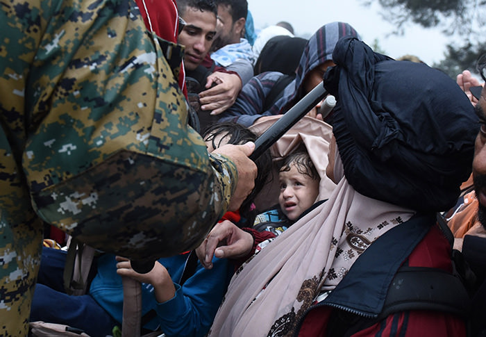A Macedonian border policeman ask refugees and migrants to stay back as they wait to pass from the northern Greek village of Idomeni to southern Macedonia (AP Photo)