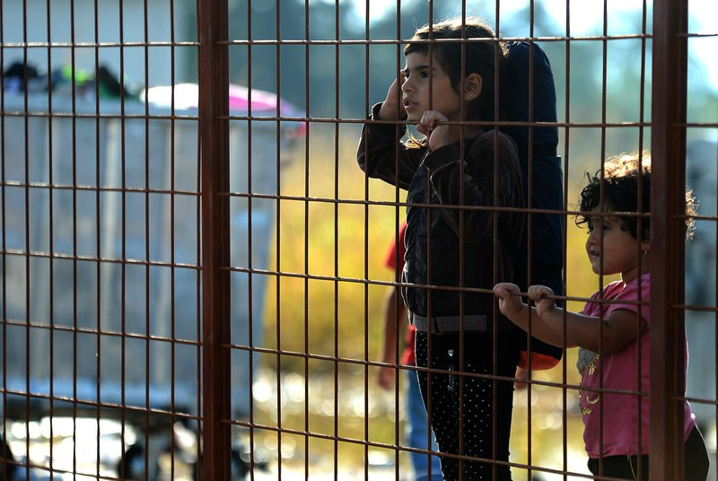 Children wait behind a fence to pass with their families in the southern Macedonian town of Gevgelija, Friday, Sept. 11, 2015 (AP Photo)