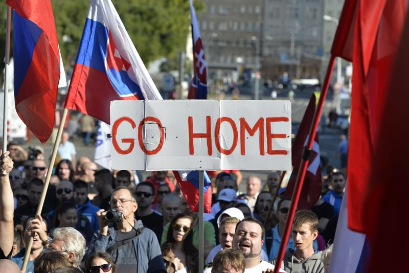 Participants hold flags and a banner during an anti-immigration rally organised by the far-right ,People's Party-Our Slovakia, on September 12, 2015 in Bratislava, Slovakia. (AFP Photo)