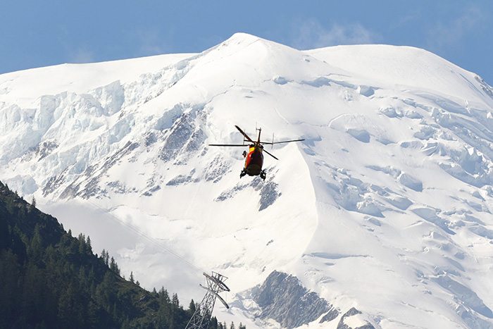 A rescue helicopter patrols the air, as part of rescue operations following an avalanche on Mont Maudit mountain, near Chamonix in the French Alps, in France, 12 July 2012 (EPA Photo)