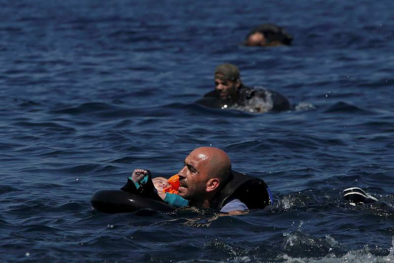 A Syrian refugee holding an infant in a lifetube as he and others swim to the Greek island of Lesbos after their dinghy deflated meters away before reaching the island from Turkish shores.