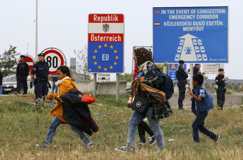 Migrants walk away from the border crossing from Hungary in Nickelsdorf, Austria.