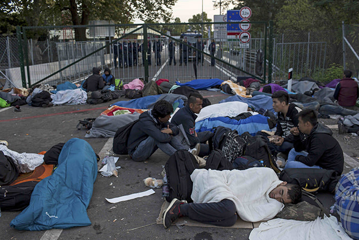 Refugees rest in front of a fence as they wait to enter Hungary, after the Hungarian police sealed the border with Serbia, September 15, 2015 (Reuters Photo)