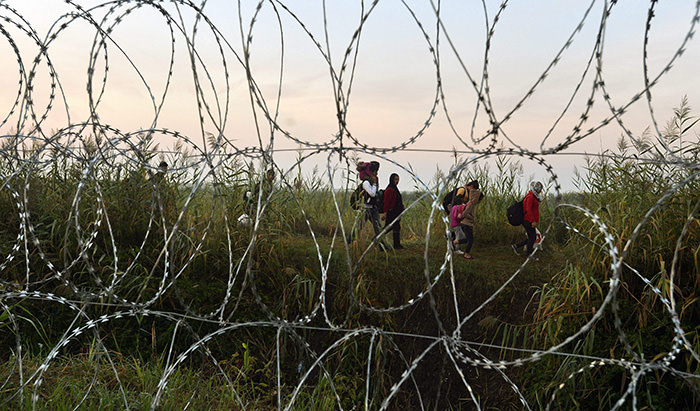 Refugees seen through razor wire fencing as they walk at the border between Serbia and Hungary, near Roszke (EPA Photo)