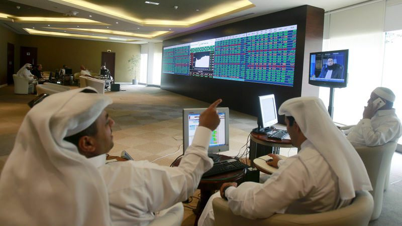 Traders watch an electronic share price display at the Doha Stock Exchange in downtown Doha.