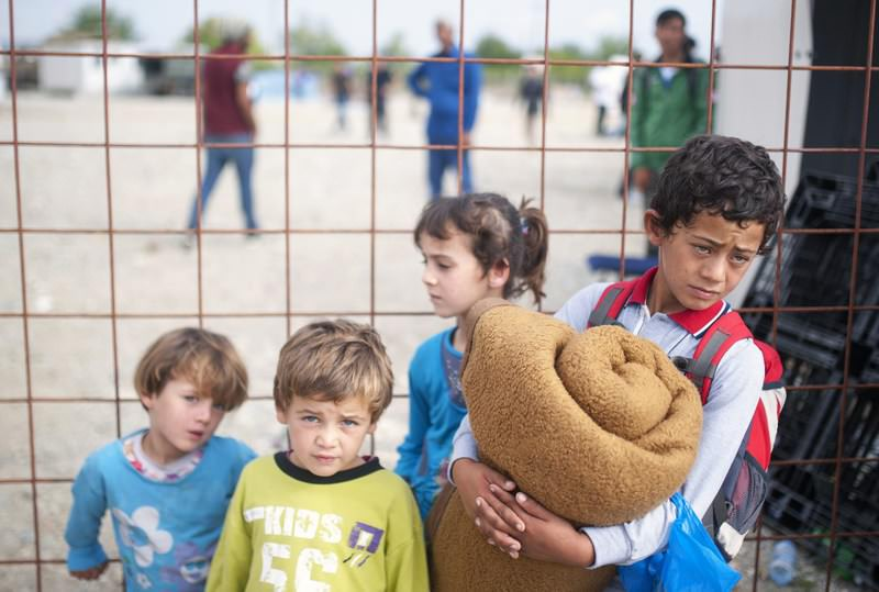 Children stand next to a fence as migrants and refugees wait in a camp to register after crossing the Macedonian-Greek border near Gevgelija.