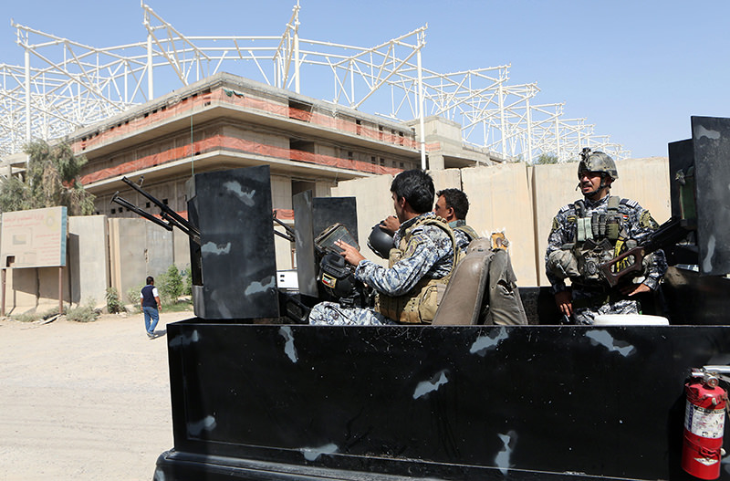 Iraqi security forces guard the entrance to a sports complex being built by a Turkish construction company, in the Shiite district of Sadr City, Baghdad, Iraq (AP Photo)