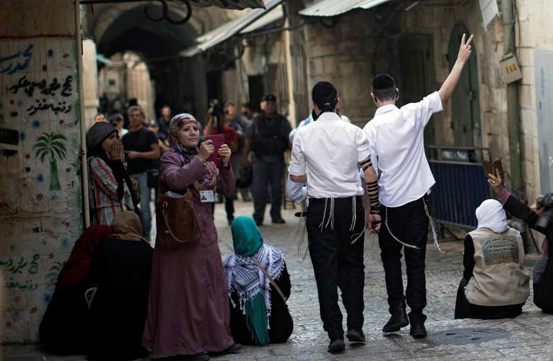 Two Jewish extremists making a V sign while passing in front of Palestinians in Old Jerusalem.
