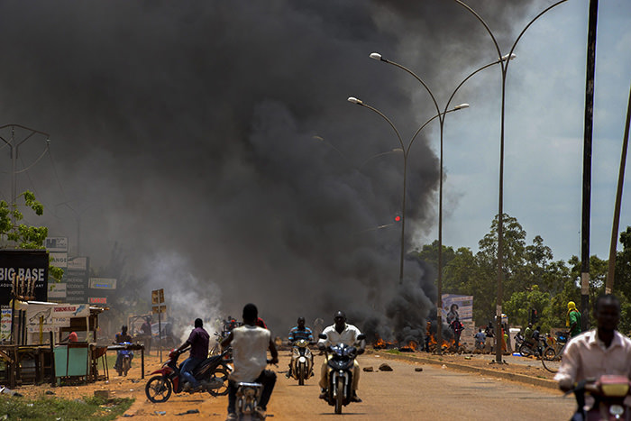 Commuters flee from burning baricades during protests against a coup in Ouagadougou, Burkina Faso, 17 September 2015 (EPA Photo)