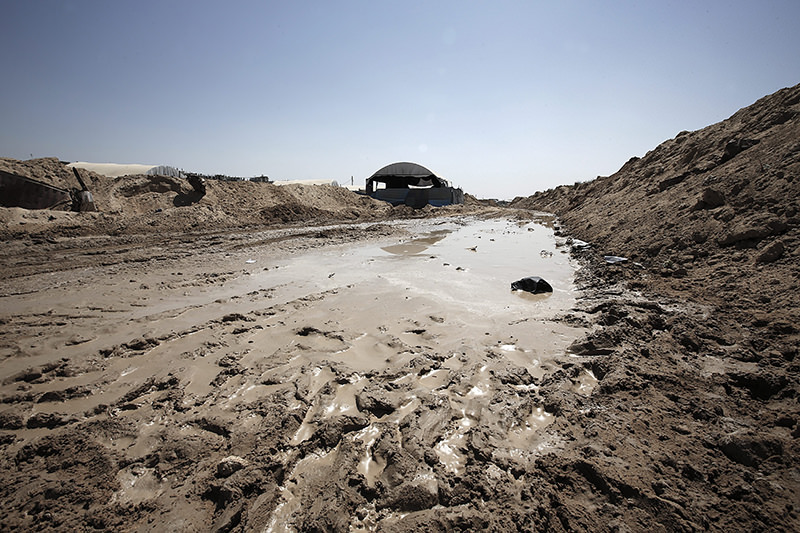 A puddle of water is seen next a tent above the entrance to a tunnel after Egyptian forces flooded smuggling tunnels beneath the border to the Gaza strip, in Rafah (EPA Photo)