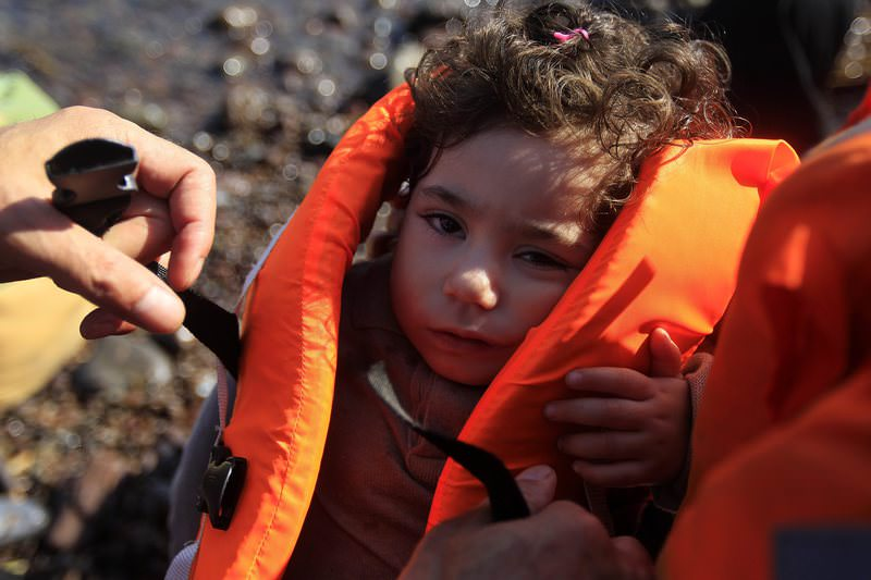 A father takes off a life jacket from his son after they arrive at the coast of Mytilini, Lesvos island, on a dinghy after crossing from Turkey, 14 September 2015.  (EPA Photo)