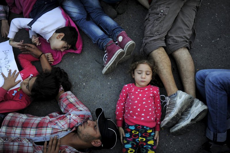 Migrants lie in protest, paying tribute to Aylan Kurdi, the drowned Syrian child whose body washed up on a beach in Turkey, as they are stopped by security forces at a bus station in Istanbul.