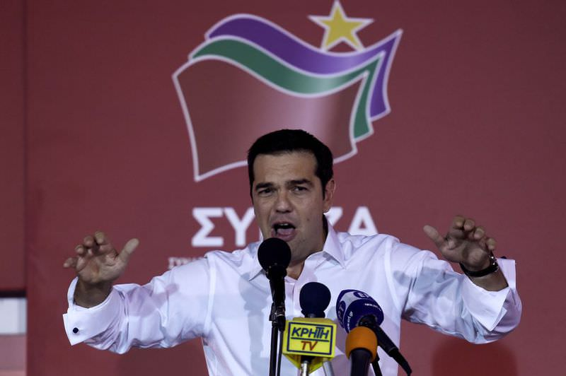 Leader of the Greek radical-left Syriza party Alexis Tsipras speaks to supporters as he arrives at the main party's election headquarters in central Athens.