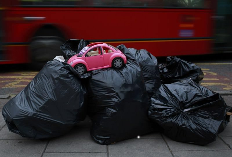 A toy model of a Volkswagen Beetle is seen on top of bags of rubbish ready for collection by waste collectors early in the morning outside a charity shop in London, United Kingdom.