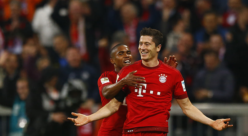 Bayern's Robert Lewandowski, right, celebrates with teammate Douglas Costa after scoring during the German Bundesliga soccer match between FC Bayern Munich and VfL Wolfsburg (AP Photo)