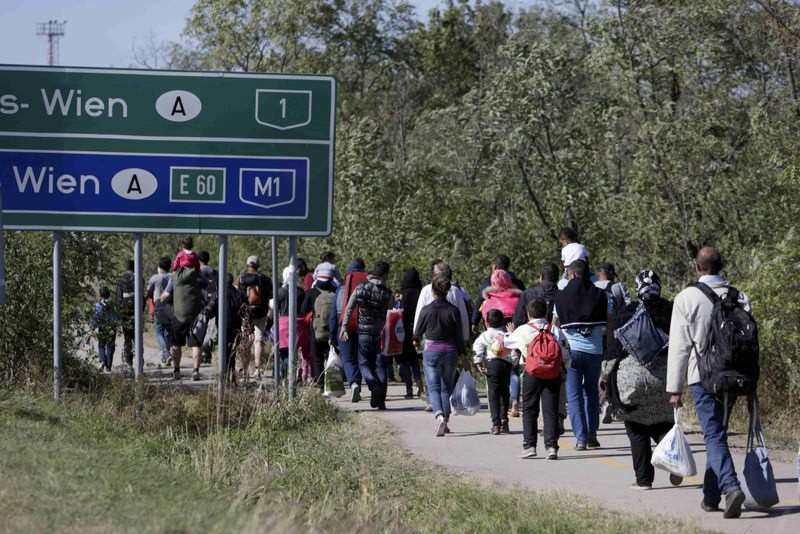 Refugees walk toward the border crossing with Austria in Hegyeshalom, Hungary.