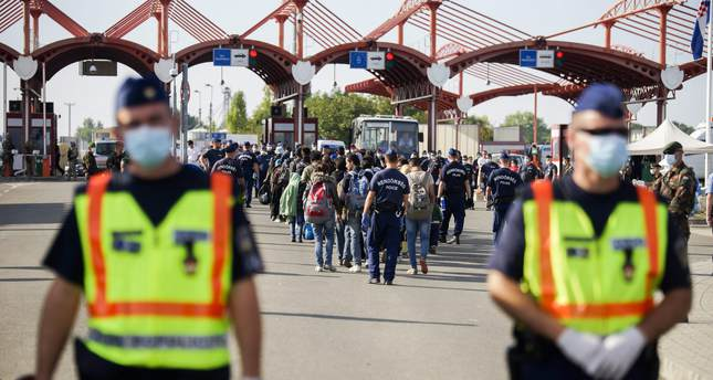 Refugees who came to Croatia by bus walk towards Hungarian buses at the border crossing between Hungary and Croatia at Beremend September 23, 2015. (EPA Photo)
