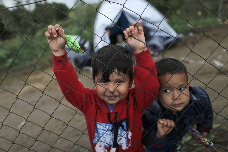 Children look through a fence as migrants wait to cross the border from Serbia into Croatia, near the village of Babska, Croatia September 25, 2015. (REUTERS Photo)