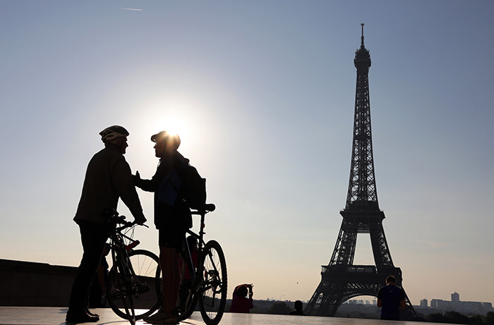 Two men with bikes chating in front of the Eiffel Tower before taking part in the day's ,Journey without cars, event taking place in the French capital Paris (AFP Photo)