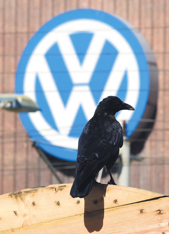 A crow sits in front of a logo of German car maker Volkswagen in Wolfsburg.