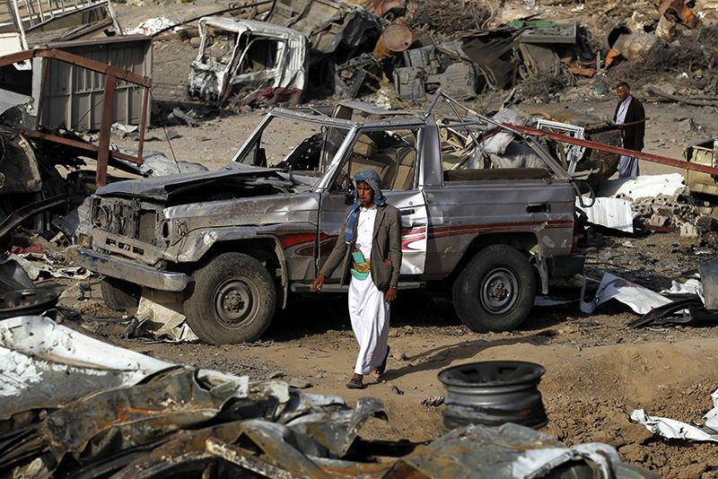 A Yemeni man walks past vehicles destroyed by a Saudi-led air strike targeting a neighborhood in Sanau2019a, Yemen, 20 September 2015 (EPA Photo)