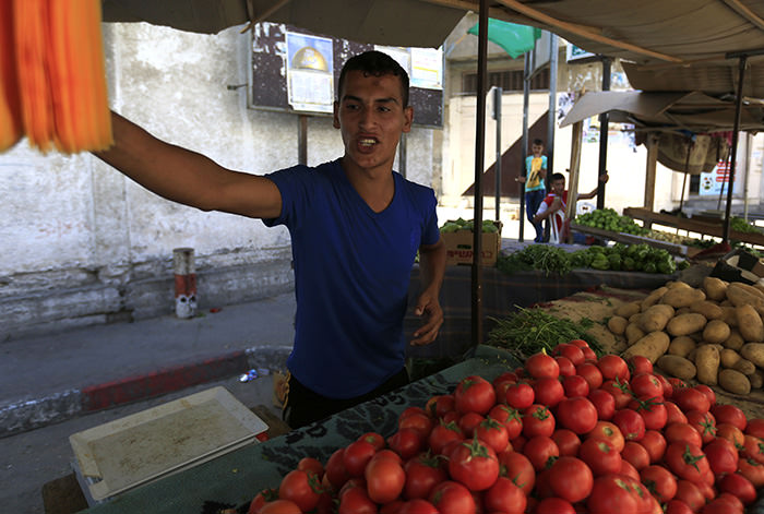 A picture taken on September 29, 2015 shows Gaza City's well known street vendor Muammar Quider, selling vegetables at his stall (AFP Photo)