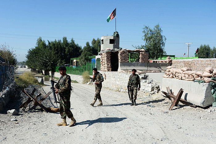 Afghan security personnel walk outside Jalalabad Airport where a US C-130 military transport plane crashed in Jalalabad on October 2, 2015 (AFP Photo)