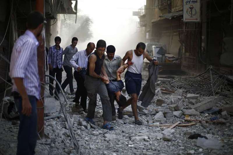 Syrians carry a wounded man following reported airstrikes on the rebel-held town of Douma on Friday.