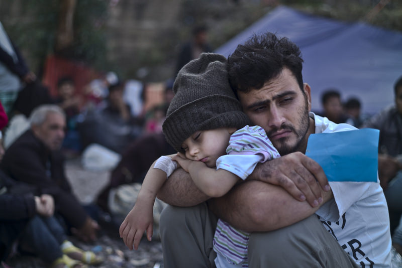 A Syrian refugee child sleeps on his father's arms while waiting to board a bus, after arriving on a dinghy from the Turkish coast to Greece, Oct. 4 , 2015. (AP Photo)