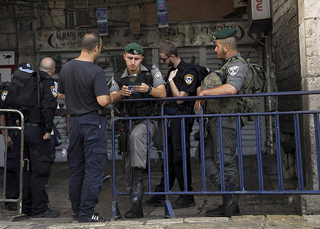 An Israeli border policeman checks papers at the entrance to the Old City in Jerusalem on Sunday, Oct. 4, 2015. (AP Photo)