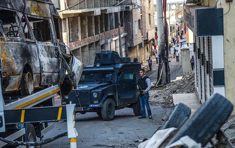 A picture taken on October 5, 2015 shows destroyed vehicles as a Turkish police officer guards a street in Silvan, after clashes between Turkish army and PKK terrorists (AFP Photo)