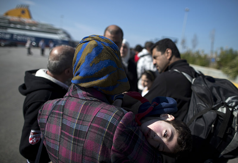 Syrian refugees wait for a bus after they arrived by ferry from Lesbos island to the port of Piraeus, near Athens, on Tuesday, Oct. 6, 2015 (AP photo)