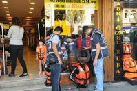 Police officers inspect life vests sold in a department store in İzmir. Life vests are ubiquitous in the city where their trade proved lucrative for local businesses.