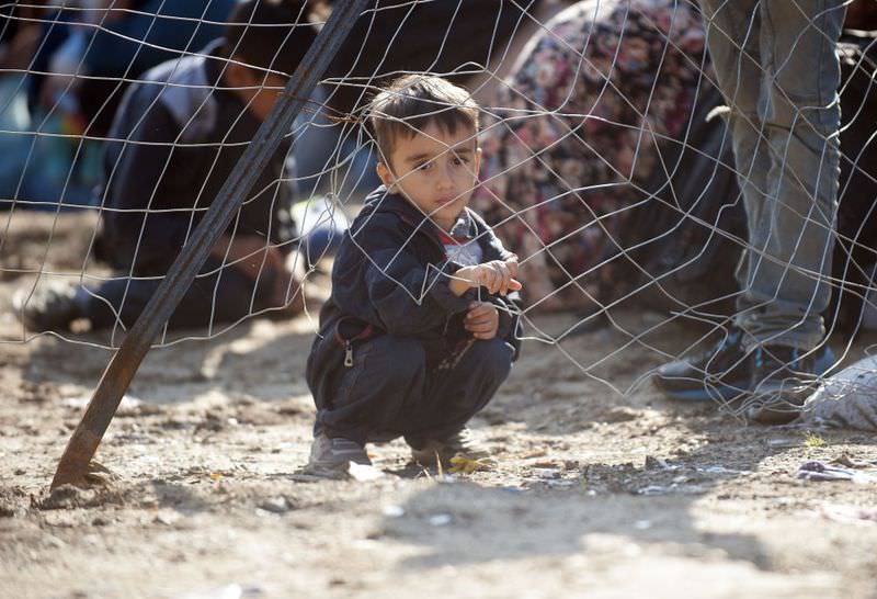 A refugee child waits with refugees wait behind a gate for Macedonian police to allow them to cross into Macedonia at the Greek border near the town of Gevgelija