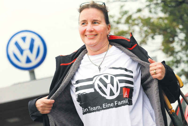 An employee poses while wearing a union T-shirt prior to a Volkswagen staff meeting in Wolfburg, yesterday.