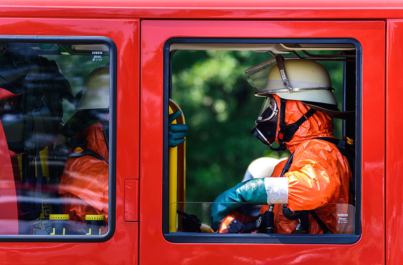 Fireworkers with protective gear sit in a fire engine at Engelmannsreuth near Bayreuth, southern Germany, on Aug 11, after US F-16 fighter jet crashed in forest close to village (AFP photo)