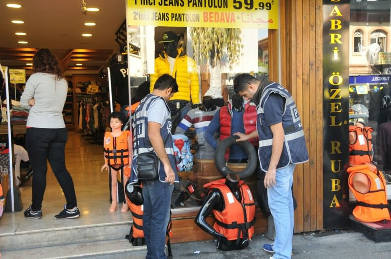 Police officers inspect life vests sold in a department store in u0130zmir. Life vests are ubiquitous in the city where their trade proved lucrative for local businesses.