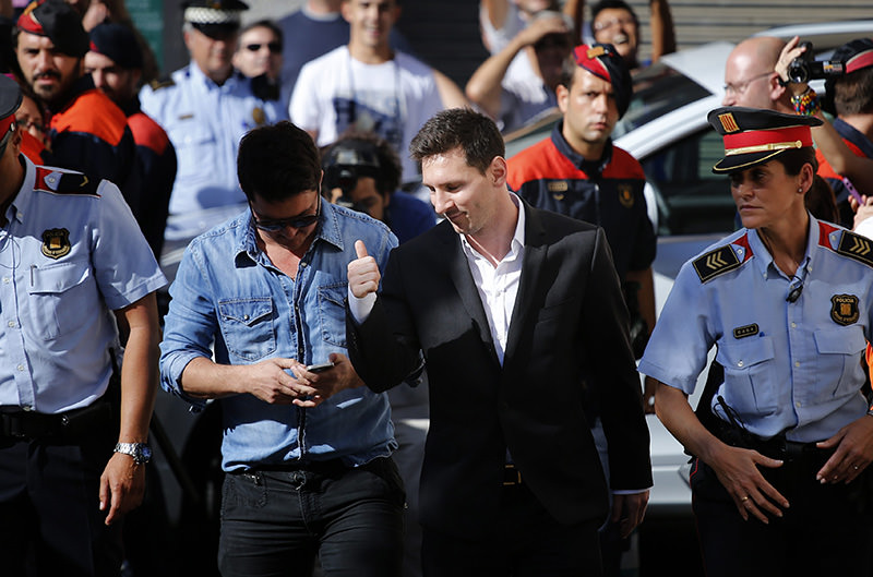 Barcelona F.C. soccer player Lionel Messi, centre right, gestures, as he arrives at a court to answer questions in a tax fraud case, in Gava, near Barcelona (AP Photo)