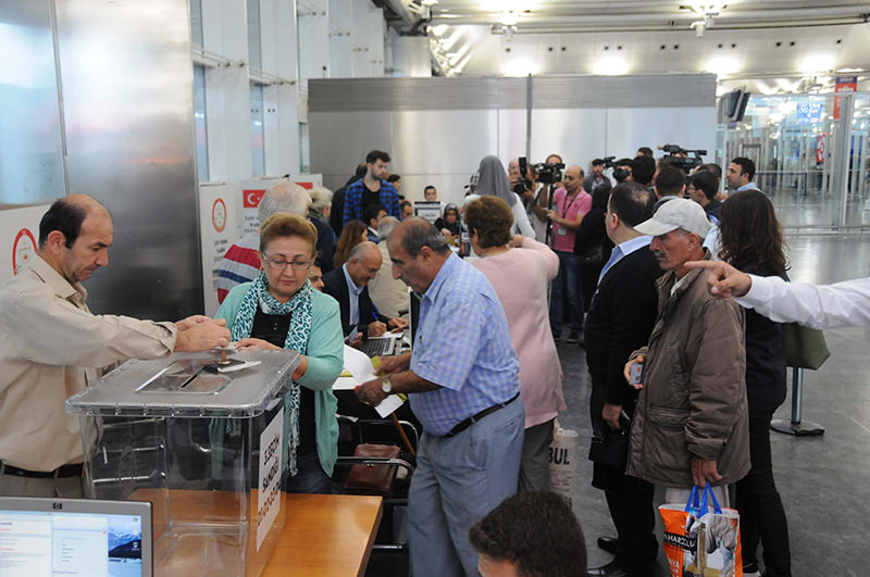 The first Turkish citizen (Sema Aslantau015f) casts her ballot at Atatu00fcrk Airport on October 8, 2015 (DHA Photo)