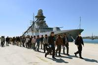 In this file picture rescued migrants walk along the quayside after disembarking from the Italian Navy vessel Bettica as they arrive in the Sicilian harbour of Augusta on April 22, 2015. (AFP Photo)