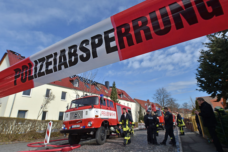 Picture taken on April 7, 2015 shows members of fire brigade working at the scene of a fire in a house planned to host a asylum seekers home in the small town of Troeglitz, Germany (AFP photo)