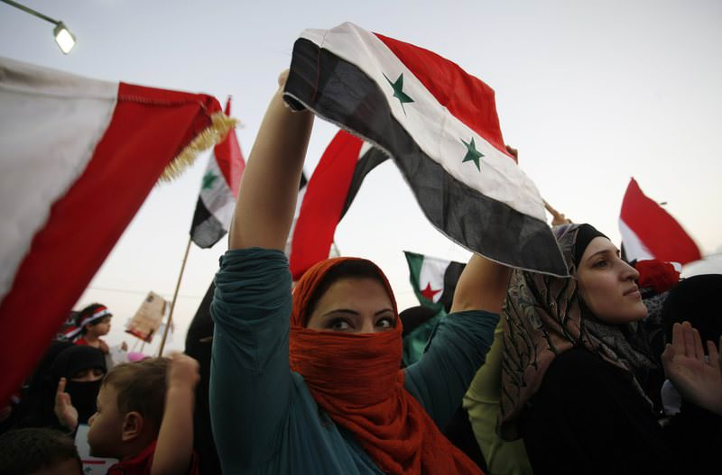 Syrian women hold the national flag and protest in front of the Syrian embassy condemning the killing and torturing women in Syria by Bashar al-Assad's regime, in Amman, Jordan, Thursday, Sept. 29, 2011. (AP Photo)