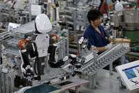 A humanoid robot works side by side with employees in the assembly line at a factory of Glory Ltd., a manufacturer of automatic change dispensers, in Kazo, north of Tokyo, Japan (Reuters Photo)