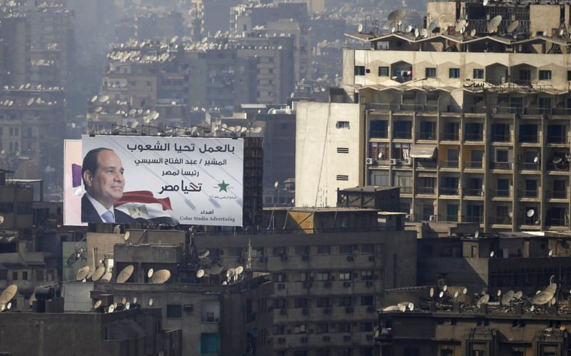 An election campaign billboard of presidential candidate and former army chief Abdel Fattah al-Sissi is seen on top of a building in Cairo, alongside narrow houses and factories.