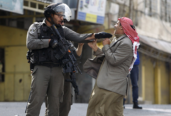 A Palestinian man argues with an Israeli border policeman during clashes in the West Bank city of Hebron October 10, 2015 (Reuters Photo)