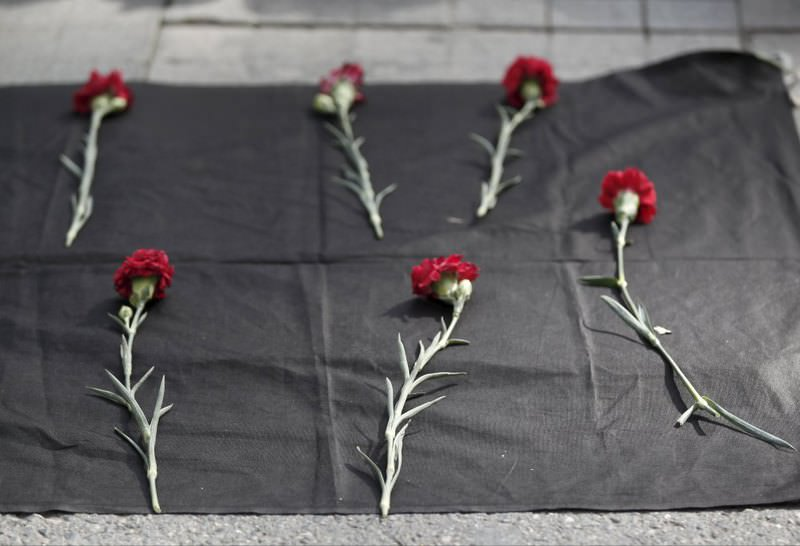 Carnations are seen placed on the ground during a protest against the latest terrorist attacks in Ankara.